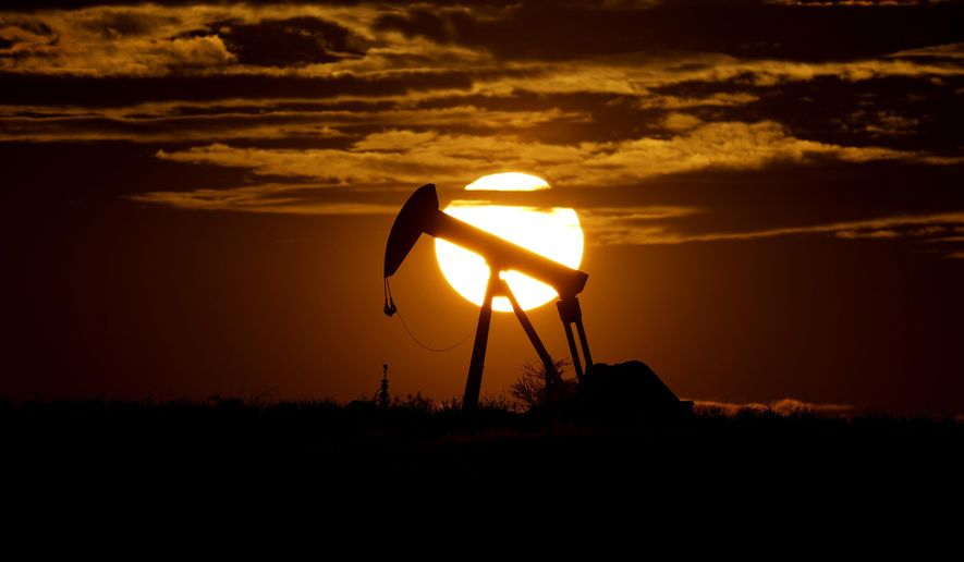 In this Wednesday, April 8, 2020, file photo, the sun sets behind an idle pump jack near Karnes City, Texas. (AP Photo/Eric Gay, File)