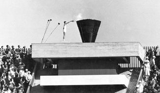 FILE - In this Oct. 10, 1964, file photo, Japanese runner Yoshinori Sakai lights the Olympic cauldron during the opening ceremony of the 1964 Summer Olympics in Tokyo. Sakai was born in Hiroshima on Aug. 6, 1945, the day the nuclear weapon destroyed that city. The 1964 Tokyo Olympics are being remembered fondly following the postponement until 2021 of the Tokyo 2020 Games. The '64 Olympics were the first to be televised internationally using communication satellites. (AP Photo/File)