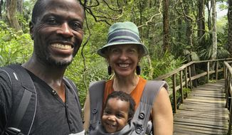 This Sept. 13, 2019 photo provided by the family shows Adebambo Alli, left, Robin Gallite and their adopted daughter, Adenike-Rae, at the Lekki Conservation Center, a natural reserve protecting the wetlands of the Lekki peninsula in Nigeria. Stranded in Nigeria for months, the couple had a rare chance to board a U.S-bound evacuation flight amid the coronavirus outbreak. They refused to fly because Adenike-Rae has yet to receive a U.S. visa and they would have had to leave her behind. (Adebambo Alli via AP)
