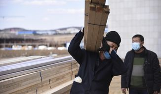 This April 10, 2020, photo released by China's Xinhua News Agency shows laborers wearing face masks to protect against the spread of the new coronavirus at an office building being converted into a temporary hospital in Suifenhe in northeastern China's Heilongjiang Province. China is facing a new coronavirus flare-up along its remote northern border with Russia, far from the epicenter of Wuhan where it has all but declared victory in the battle against the pandemic. The northern frontier has been sealed and emergency medical units were rushed to the area to fend off the threat from people bringing the virus back from abroad. (Dong Baosen/Xinhua via AP)