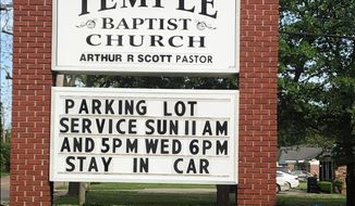 This image provided by Alliance Defending Freedom shows the sign for parking lot church services outside of Temple Baptist Church in Greenville, Miss., on April 9, 2020. The Justice Department has weighed in on a local Mississippi case involving a church that says its religious freedoms were violated. Temple Baptist in Greenville has been holding drive-in services for congregants during the coronavirus outbreak.  (Alliance Defending Freedom via AP)