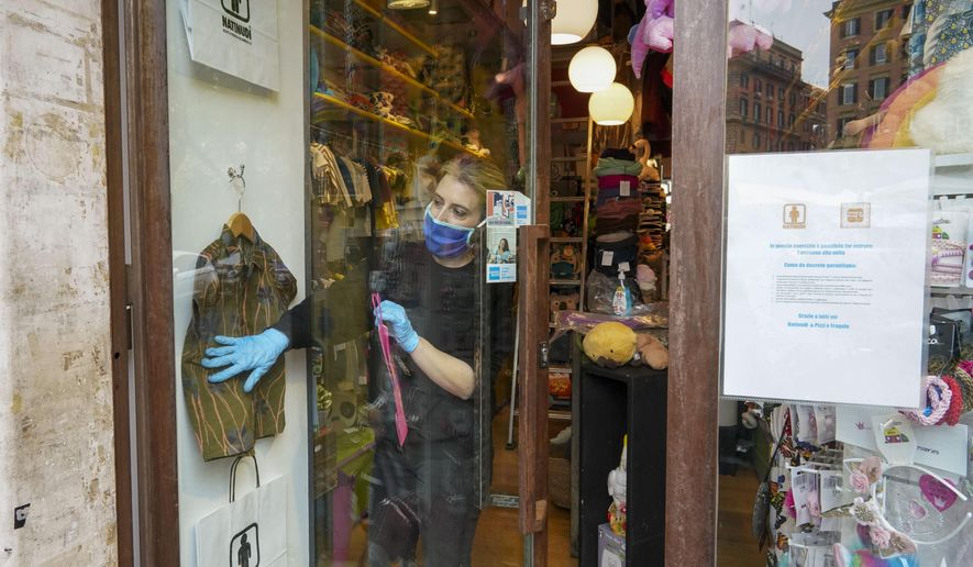 Camilla Cocchi wears a face mask and gloves as she sorts out clothing in her children's clothes shop after it was allowed to reopen following lockdown measures to contain the spread of Covid-19, in Rome, Tuesday, April 14, 2020. In Italy, bookstores, stationary stores and shops selling baby clothes and supplies were allowed to open nationwide on Tuesday, provided they could maintain the same social-distancing and sanitary measures required in supermarkets. The new coronavirus causes mild or moderate symptoms for most people, but for some, especially older adults and people with existing health problems, it can cause more severe illness or death. (AP Photo/Andrew Medichini)