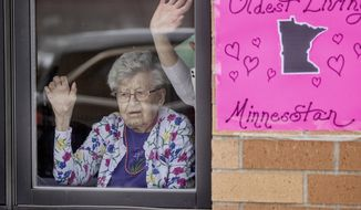 Friends and family celebrated the 112th birthday of Erna Zahn with a parade in front of her window at the Oak Hills Living Center, Tuesday, April 14, 2020 in New Ulm, Minn. Zahn is Minnesota's oldest resident. (Elizabeth Flores/Star Tribune via AP)