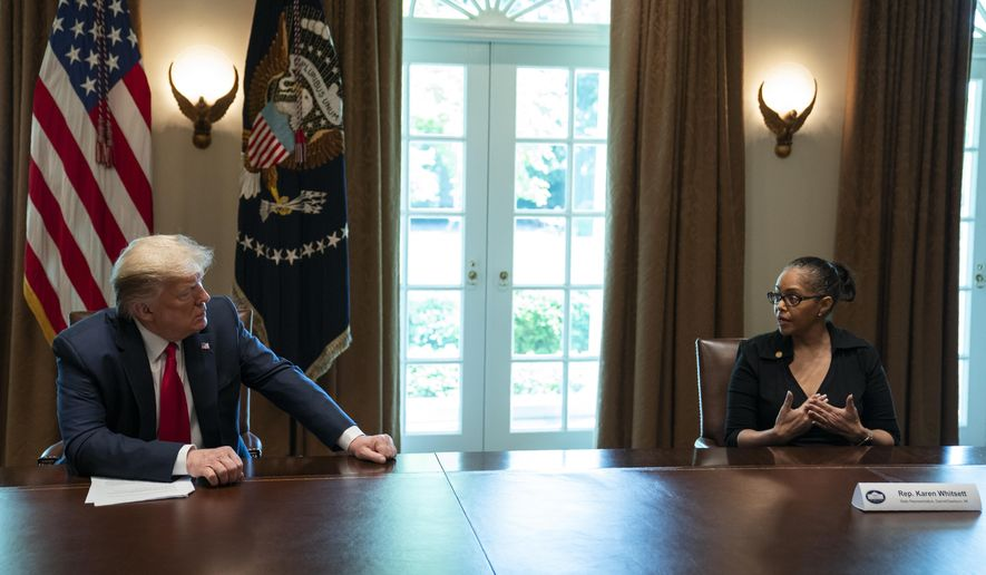 President Donald Trump listens as Karen Whitsett shares her story of recovery from COVID-19, in the Cabinet Room of the White House, Tuesday, April 14, 2020, in Washington. (AP Photo/Evan Vucci)