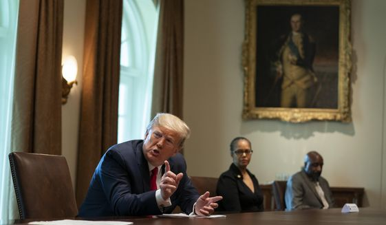 Michigan state Rep. Karen Whitsett, center, and her husband Jason Whitsett, right, listen as President Donald Trump speaks during a meeting with people that have recovered from COVID-19, in the Cabinet Room of the White House, Tuesday, April 14, 2020, in Washington. (AP Photo/Evan Vucci)
