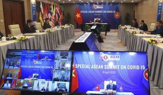 Vietnamese Prime Minister Nguyen Xuan Phuc, background, addresses ASEAN leaders during the Special ASEAN summit on COVID-19 in Hanoi, Vietnam Tuesday, April 14, 2020. ASEAN leaders and their counterparts from China, Japan and South Korea hold the summit online to discuss actions coping with the COVID-19 pandemic. (AP Photo/Hau Dinh)