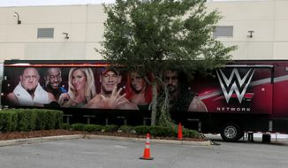 A trailer set up near a satellite truck to transmit wrestling broadcasts is parked outside the WWE Performance Center Tuesday, April 14, 2020, in Orlando, Fla. Florida's top emergency official last week amended Gov. Ron DeSantis' stay-at-home order to include employees at the professional sports and media production with a national audience, if the location is closed to the public.  (AP Photo/John Raoux)