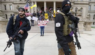 Protesters carry rifles near the steps of the Michigan State Capitol building in Lansing, Mich., Wednesday, April 15, 2020. Flag-waving, honking protesters drove past the Michigan Capitol on Wednesday to show their displeasure with Gov. Gretchen Whitmer's orders to keep people at home and businesses locked during the new coronavirus COVID-19 outbreak. (AP Photo/Paul Sancya)