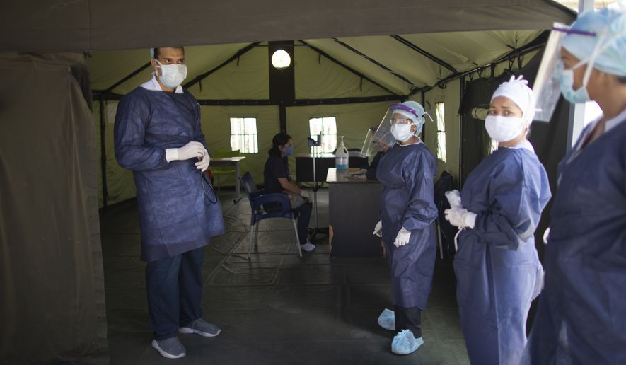 Venezuelan doctors stand at the entrance of a tent set up at the Ana Francisca Perez de Leon hospital for people get a free, quick coronavirus test amid a quarantine to help stop the spread of COVID-19 in Caracas, Venezuela, Wednesday, April 15, 2020. (AP Photo/Ariana Cubillos)