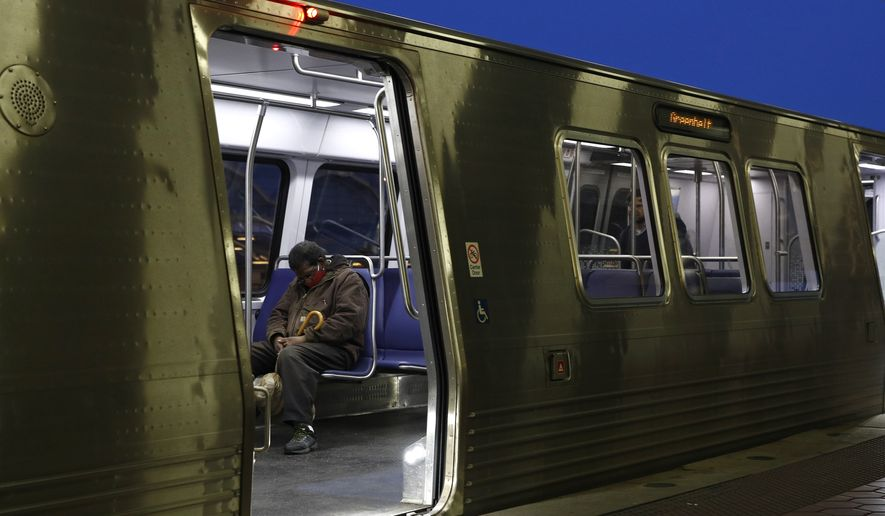 In this file photo, a man wears a face mask to protect against the spread of the new coronavirus as he sits on a Metro train, Wednesday, April 15, 2020, at the Ronald Reagan Washington National Airport Metro station in Arlington, Va.  (AP Photo/Patrick Semansky)  **FILE**