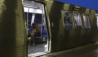 A man wears a face mask to protect against the spread of the new coronavirus as he sits on a Metro train, Wednesday, April 15, 2020, at the Ronald Reagan Washington National Airport Metro station in Arlington, Va. The District of Columbia metro region is under a stay-home order for all residents in an effort to slow the spread of the new coronavirus. (AP Photo/Patrick Semansky)