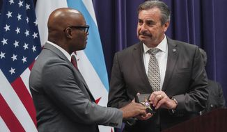 Interim Chicago Police Department Superintendent Charlie Beck, right, presents David Brown Sr., the acting superintendent, with the superintendent's badge at Beck's farewell ceremony Wednesday, April 15, 2020. Brown is a former Dallas police chief. (Annie Costabile/Chicago Sun-Times via AP)