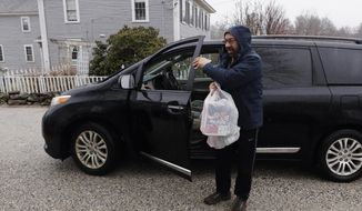FILE - In this Friday, April 3, 2020, file photo, Instacart worker Arthur Berte delivers groceries to a home in East Derry, N.H. Some app-based delivery companies have announced hiring sprees, including Instacart, to cope with a surge in orders from millions of people stuck at home. (AP Photo/Charles Krupa, File)