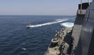 In this Wednesday, April 15, 2020, photo made available by U.S. Navy, Iranian Revolutionary Guard vessels sail close to U.S. military ships in the Persian Gulf near Kuwait. (U.S. Navy via AP) **FILE**