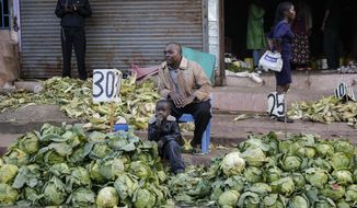 In this March 24, 2020, file photo, a street trader sells cabbages by the side of the road, after the government ordered the closure of the main open-air market, in the Mathare slum, or informal settlement, of Nairobi, Kenya. Lockdowns in Africa limiting the movement of people in an attempt to slow the spread of the coronavirus are threatening to choke off supplies of what the continent needs the most: Food. (AP Photo/Brian Inganga, File)
