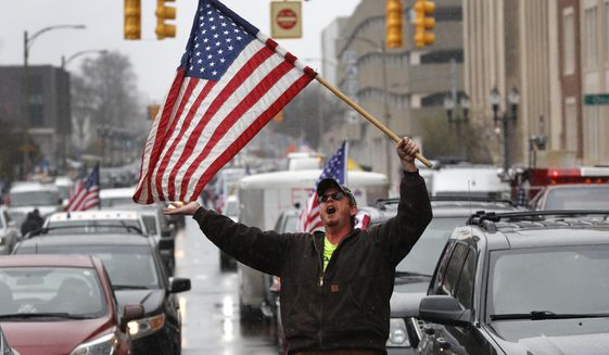 Christopher Merrill protests at the State Capitol in Lansing, Mich., Wednesday, April 15, 2020. Flag-waving, honking protesters drove past the Michigan Capitol on Wednesday to show their displeasure with Gov. Gretchen Whitmer's orders to keep people at home and businesses locked during the new coronavirus COVID-19 outbreak. (AP Photo/Paul Sancya)