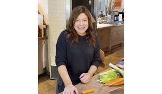 """In this undated photo made available by the Rachael Ray Show, Rachael Ray cooks in her home kitchen in upstate New York. Ray is taping """"#STAYHOME With Rachael"""" two days a week from her home. (Ronde Colleta/Rachael Ray Show via AP)"""