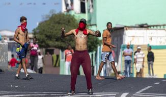 Residents of Mitchell's Plain in Cape Town, South Africa, Clash with police Tuesday, April 14, 2020, in protest against the distribution of food parcels to the poor and unemployed during the third week of a lockdown to control the spread of coronavirus. (AP Photo)