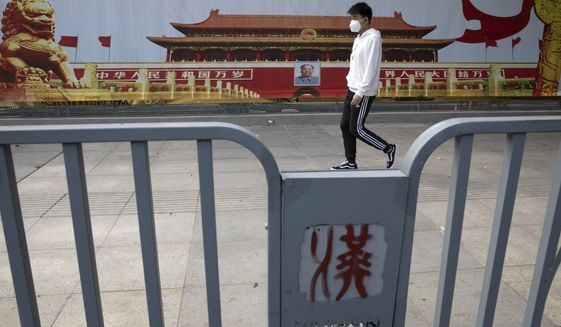 A resident wearing a mask against coronavirus walks past government propaganda poster featuring Tiananmen Gate in Wuhan in central China's Hubei province Thursday, April 16, 2020.  (AP Photo/Ng Han Guan)
