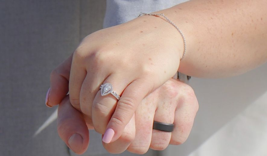 In this Friday, April 10, 2020, photo provided by Amy Fowler Shores, Savannah Kulenic and Dylan Perkins hold hands during their wedding ceremony on a North Carolina beach. A jewelry company said it could overnight the groom's ring, but it was going to arrive after the ceremony. FedEx driver Joe Engel saw a note on the bride's door and took the package to the beach just in time. The couple was supposed to get married in Hawaii but canceled their destination ceremony amid the coronavirus pandemic. (Amy Fowler Shores via AP)