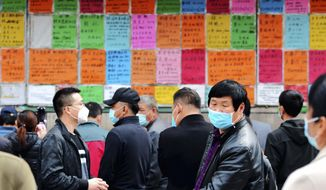 In this April 8, 2020 photo, laborers wear facemasks to protect against the spread of the new coronavirus as they look at job postings at a labor market in Qingdao in eastern China's Shandong Province. China has reported its biggest economic decline since the 1970s as it fought the coronavirus in the first quarter of the year. (Chinatopix via AP)