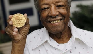 In this July 20, 2012 file photo, Carmen Williamson, the first black boxing referee and judge at an Olympic games, poses with his honorary gold medal in his hometown of Toledo, Ohio. Family members say Williamson  died from COVID-19 complications on April 8, 2020 at a hospital in Toledo.    (Zack Conkle/The Blade via AP)