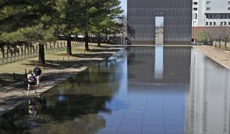 FILE - In this March 18, 2020 file photo, visitors walk next to the reflecting pool at the Oklahoma City National Memorial and Museum in Oklahoma City. The Oklahoma City National Memorial and Museum has announced that it will offer a recorded, one-hour television program in place of a live ceremony to mark the 25th anniversary of the Oklahoma City bombing due to concerns about the spread of the coronavirus. (AP Photo/Sue Ogrocki, File)