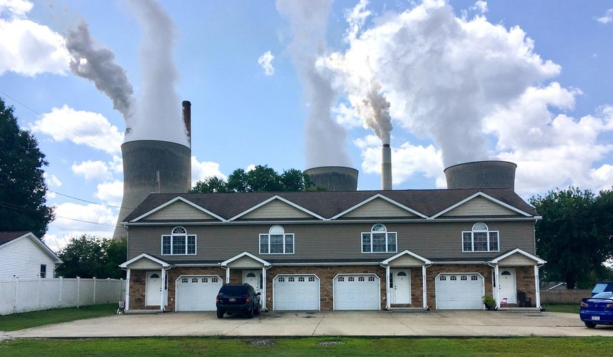 In this Aug. 23, 2018, file photo, a coal-fired plant in Winfield, W.Va, is seen from an apartment complex in the town of Poca across the Kanawha River. The Trump administration is gutting an Obama-era rule that compelled coal plants to cut back emissions of mercury and other human health hazards, limiting future regulation of air pollutants by petroleum and coal plants. (AP Photo/John Raby, File)