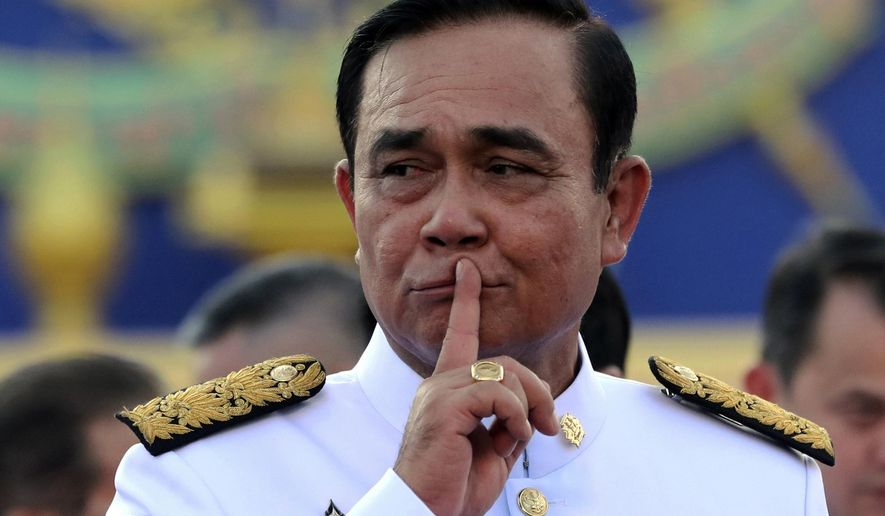 FILE - In this July 16, 2019, file photo, Thailand's Prime Minister Prayuth Chan-ocha gestures after a group photo with his cabinet members at the government house in Bangkok, Thailand. As governments across the world enact emergency measures to keep people at home and stave off the pandemic, some are unhappy about having their missteps publicized. Others are taking advantage of the crisis to silence critics and tighten control. (AP Photo/Sakchai Lalit, File)