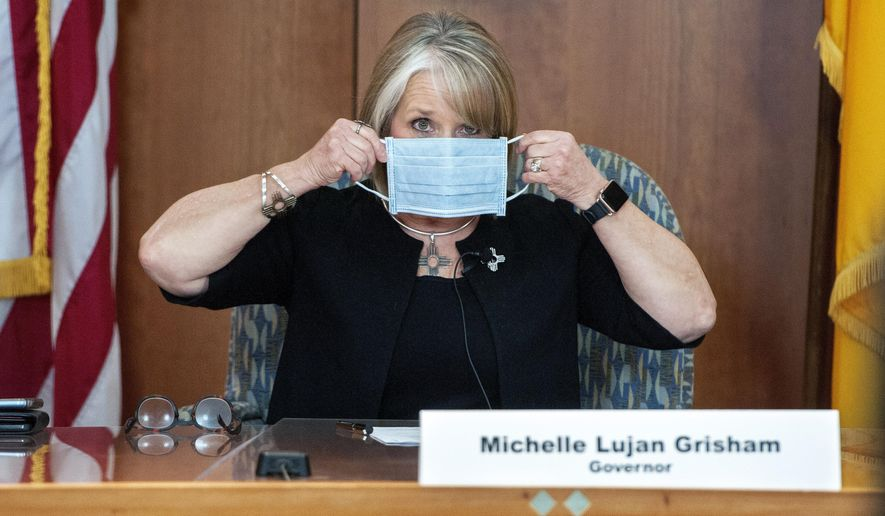 New Mexico Gov. Michelle Lujan Grisham puts on her face mask when not speaking during an update on the COVID-19 outbreak in the state during a news conference in the state Capitol in Santa Fe, N.M., Wednesday, April 15, 2020. (Eddie Moore/The Albuquerque Journal via AP, Pool)