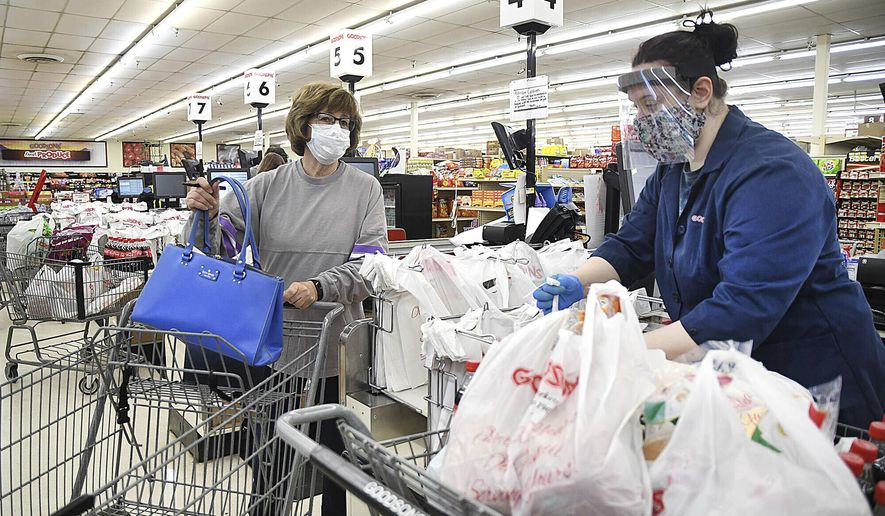 Delores Browning, lefdt, waits for Molly Stanley to bag her groceries at Goodson's Supermarket in Oceana, W.Va. Wednesday, April 8, 2020. On Tuesday, the health department reduced the number shoppers to only 10 at a time. Goodson's supplied their employees each with face masks and most chose to wear them and they also offered to shop for their customers avoiding long wait times to enter the store. (Rick Barbero/The Register-Herald via AP)