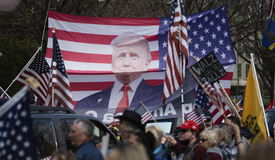 "A banner of President Trump on an American flag is held above a crowd demanding the state's Stay at Home order be lifted during a ""Liberate Minnesota"" protest in St. Paul, Minn., on Friday, April 17, 2020. A growing number of protests are being staged across the U.S. to oppose stay-at-home orders amid the coronavirus pandemic. (Evan Frost/Minnesota Public Radio via AP)"