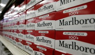 FILE- This June 14, 2018, file photo shows cartons of Marlboro cigarettes on the shelves at JR outlet in Burlington, N.C.  Altria Group says that Chairman and CEO Howard Willard, who was recovering from COVID-19, has retired, Friday, April 17, 2020. Altria, the maker of Marlboro cigarettes, did not say if the 56-year-old Willard's retirement was related to his illness.(AP Photo/Gerry Broome, File)
