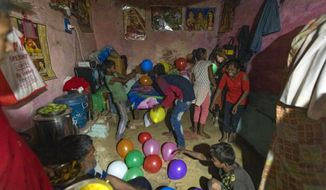 In this April 3, 2020, photo, Rajesh Dhaikar's children play with balloons in their house in Prayagraj, India. Dhaikar has a small balloon stall in a nearby market, selling plastic bursts of red and blue and yellow one at a time, and rarely earning more than $2.50 a day. His wife, Suneeta, makes about $20 a month cleaning homes. They have five children, ranging in age and a bank account with about $6.50 in it. India has launched one of the most draconian social experiments in human history, locking down its entire population, including hundreds of millions of people who struggle to survive on a few dollars a day. (AP Photo/Rajesh Kumar Singh)
