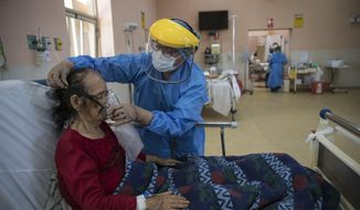 A nurse places an oxygen mask on a patient inside the intensive care unit for people infected with the new coronavirus, at the 2 de Mayo Hospital, in Lima, Peru, Friday, April 17, 2020. The new coronavirus causes mild or moderate symptoms for most people, but for some, especially older adults and people with existing health problems, it can cause more severe illness or death. (AP Photo/Rodrigo Abd)