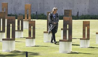 Lynne Gist walks through the Field of Empty Chairs at the Oklahoma City National Memorial and Museum, Wednesday, April 15, 2020, in Oklahoma City. Gist lost her sister, Karen Gist Carr, April 19, 1995, when a truck bomb ripped through the Alfred P. Murrah Federal Building in downtown Oklahoma City, killing 168 people. (AP Photo/Sue Ogrocki)