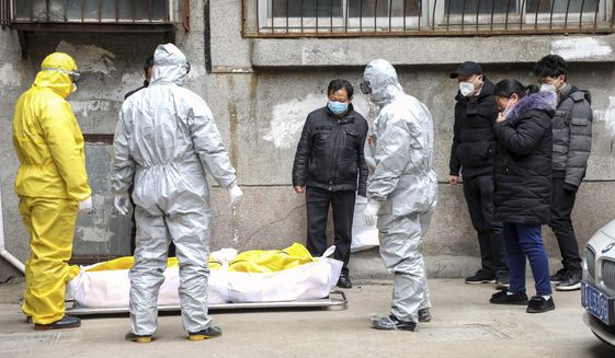 """Funeral home workers remove the body of a person suspected to have died from the coronavirus outbreak from a residential building in Wuhan in central China's Hubei Province,"""" Feb 1, 2020. The central Chinese city of Wuhan has raised its number of COVID-19 fatalities by more than 1,000. State media said the undercount had been due to the insufficient admission capabilities at overwhelmed medical facilities at the peak of the outbreak. (Chinatopix via AP) ** FILE **"""