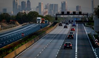 A few cars and trucks drive on the usually very crowded main highway around Frankfurt, Germany, that is seen in the background on Thursday, April 16, 2020. Due to the coronavirus the economy worldwide expects heavy losses. (AP Photo/Michael Probst)