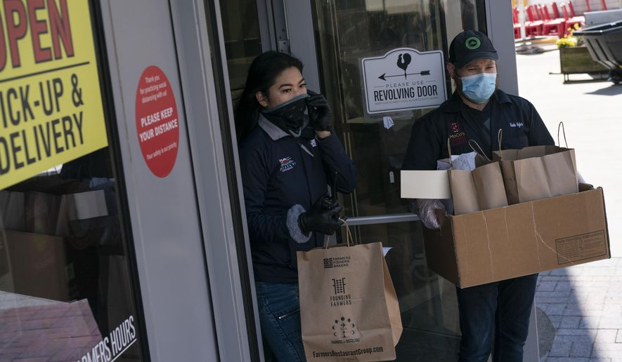 In this April 15, 2020, photo, employees, wearing protective gloves and masks, walk to-go orders to waiting cars at Founding Farmers restaurant in Potomac, Md. Founding Farmers is closed to in-restaurant dining during the coronavirus outbreak but they are providing delivery, and curbside pick-up to-go, for meals and groceries. (AP Photo/Carolyn Kaster)