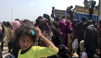 Rohingya refugees gather after being rescued in Teknaf near Cox's Bazar, Bangladesh, Thursday, April 16, 2020. Bangladesh's coast guard has rescued 382 starving Rohingya refugees who had been drifting at sea for weeks after failing to reach Malaysia, officials said Thursday. (AP Photo/Suzauddin Rubel)