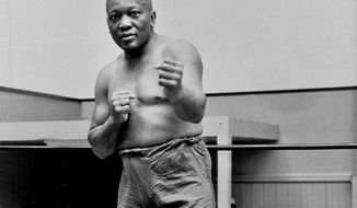 """FILE - In this 1932 file photo, boxer Jack Johnson, the first black world heavyweight champion, poses in New York City. Born on March 31, 1878, Johnson was the first black world heavyweight boxing champion, holding the title from 1908 to 1915. He remains a boxing legend, with his 1910 fight against James J. Jeffries dubbed the """"fight of the century"""". (AP Photo/File)"""