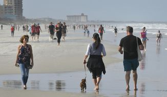 People walk on the beach during the coronavirus pandemic Friday, April 17, 2020 on Jacksonville Beach, Fla. Gov. Ron DeSantis  has given the green light for some beaches and parks to reopen if it can be done safely after being closed because of the coronavirus.  DeSantis' announcement on Friday came as north Florida beaches became among the first to allow beach-goers to return since the closures.  (Will Dickey/The Florida Times-Union via AP)