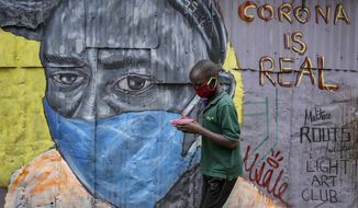 """A boy wearing a face mask carries a small bowl of """"githeri"""", or mixed beans and maize, for him to eat as he walks past an informational mural warning people about the risk of the new coronavirus, painted by graffiti artists from the Mathare Roots youth group, in the Mathare slum, or informal settlement, of Nairobi, Kenya Saturday, April 18, 2020. Africa now has more than 1,000 deaths from COVID-19, the Africa Centers for Disease Control and Prevention said Saturday, with 52 of the continent's 54 countries having reported cases. (AP Photo/Brian Inganga)"""