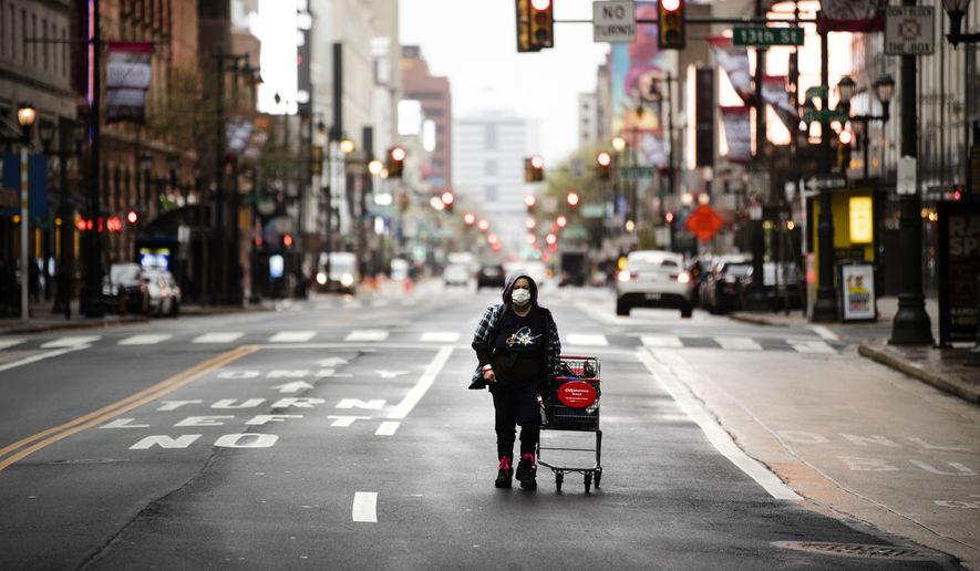 In this April 13, 2020, file photo a person wearing a protective mask walks down Market Street in Philadelphia. Across an arc of vital swing states, the coronavirus has put politics on an uneasy pause. Political fights are raging among state leaders from Iowa to Pennsylvania over the handling of the pandemics impact. (AP Photo/Matt Rourke, File)