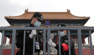 Security guards wearing protective face masks to prevent the spread of the new coronavirus lock the gate of the Forbidden City which remains closed following the new coronavirus outbreak in Beijing, Sunday, April 19, 2020. The pandemic that began in China in December is believed to have infected more than 2 million people worldwide. While most recover, at least over 150,000 have died, according to a tally by Johns Hopkins University based on figures supplied by health authorities around the globe. (AP Photo/Andy Wong)