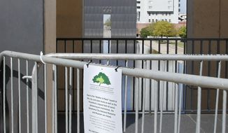The 9:02 gate at the Oklahoma City National Memorial and Museum is pictured behind a sign announcing the closure of the site, Wednesday, April 15, 2020, in Oklahoma City. Due to COVID-19 concerns, the site scaled back its plans for a 25th anniversary remembrance and will instead offer a recorded, one-hour television program that includes the reading of the names of the 168 people killed in the bombing followed by 168 seconds of silence, instead of the annual open-to-the-public ceremony. (AP Photo/Sue Ogrocki)