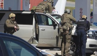 Royal Canadian Mounted Police officers surround a suspect at a gas station in Enfield, Nova Scotia, Sunday April 19, 2020. Canadian police say multiple people are dead plus the suspect after a shooting rampage across the province of Nova Scotia. It was the deadliest shooting in Canada in 30 years. (Tim Krochak/The Canadian Press via AP)