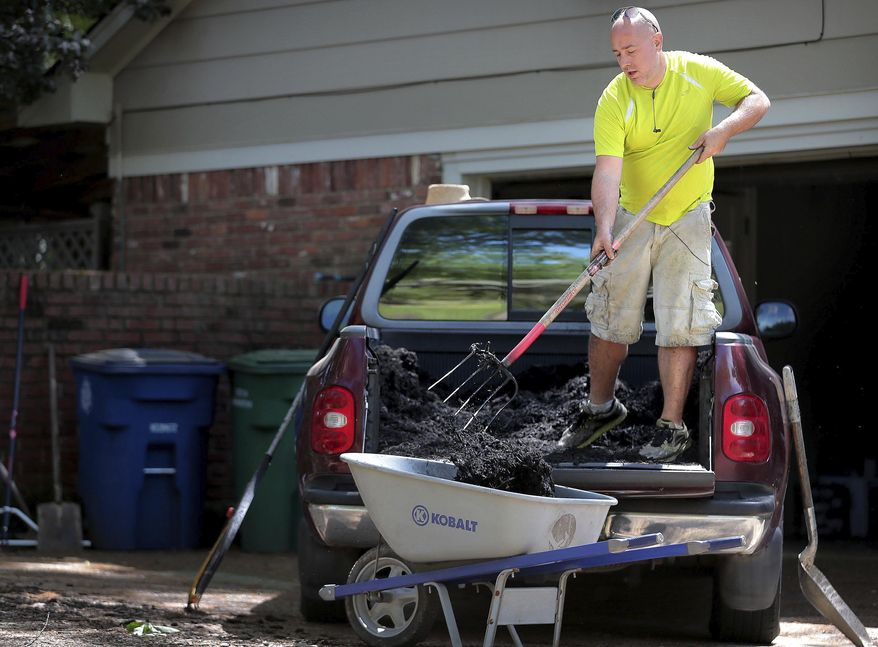 Scott Briggs shovels mulch out of the back of his borrowed truck while planting hydrangeas at a client's home in Germantown, Tenn., Saturday, April 11, 2020. Briggs is a laid-off bartender who, rather than pulling unemployment, decided to start a lawn care business called Laid Off Lawncare which has taken off with business over the first two weeks. (Jim Weber/Daily Memphian via AP)
