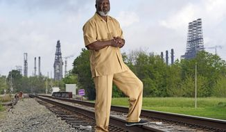 "Activist Hilton Kelley poses along the railroad tracks that divide East and West Port Arthur Monday, March 23, 2020, in Port Arthur, Texas. ""Now we may not drop dead that day,"" Kelley said of the environmental protection rollbacks, and the communities surrounding the refineries and plants. ""But when you're inundated day after day...we're dead. We're dead."" (AP Photo/David J. Phillip)"