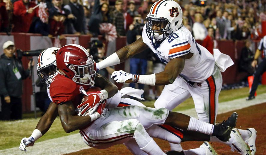 In this Nov. 24, 2018, file photo, Alabama wide receiver Henry Ruggs III (11) catches a pass for a touchdown as Auburn defensive back Roger McCreary (17) and linebacker Cameron Latu (20) defend during the second half of an NCAA college football game in Tuscaloosa, Ala. This year's NFL draft features a superb group of wide receivers, including Ruggs, who are expected to make immediate impacts in the NFL. (AP Photo/Butch Dill, File)  **FILE**